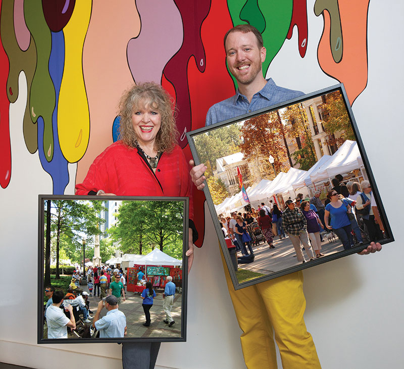Eileen and Alex Kunzman with framed paintings in front of a stylized mural of paint dripping