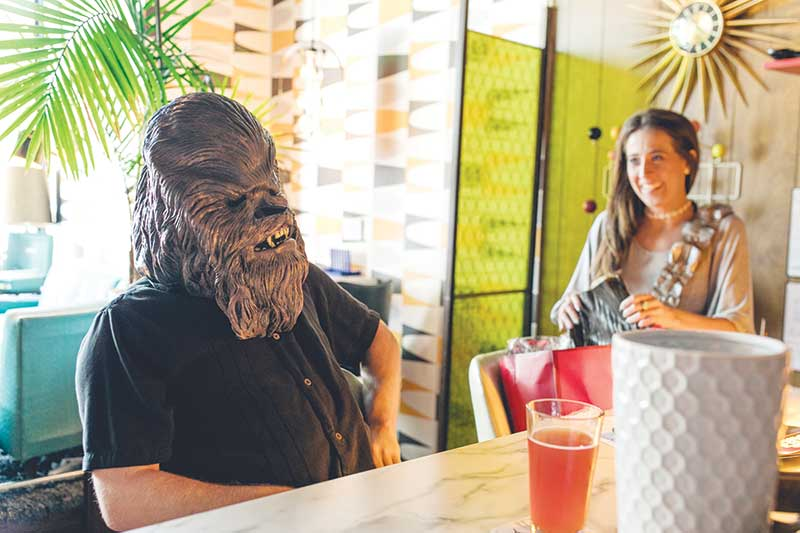 Someone sitting at a coffee counter while wearing a Chewbacca mask as a woman looks on