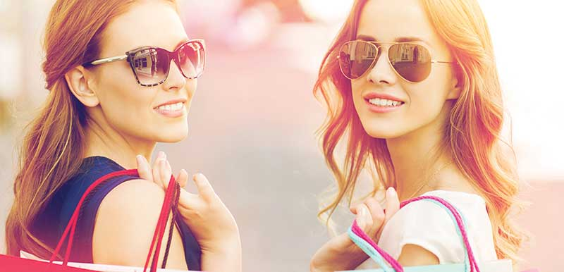 Two women in sunglasses and shopping bags smiling at the camera