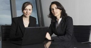 two female lawyers, one with a laptop, looking at the camera