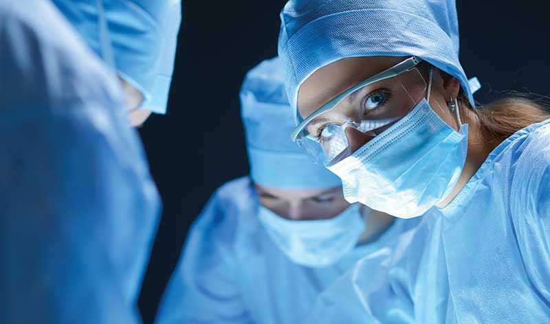 suited and masked surgeons at work, one looking at the camera